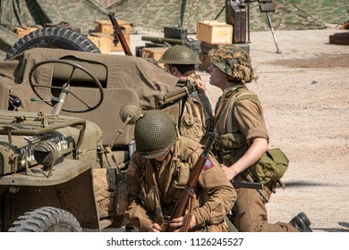 LEICESTERSHIRE,UK  - JUNE 03 2018: Men dressed in wartime US army soldiers uniform reenacting military maneuvers during Victory Day Europe Celebration Event at Great Central Railway, Quorn