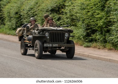 LEICESTERSHIRE,UK  - JUNE 03 2018: Men dressed in wartime US army soldiers uniform riding in military  jeeps during Victory Day Europe Celebration Event at Great Central Railway, Quorn