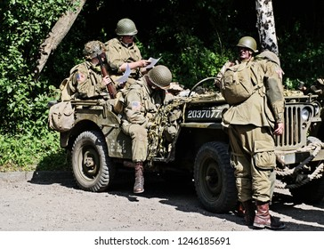LEICESTERSHIRE,UK  - JUNE 07 2015: Men dressed in wartime US army soliders uniform around a jeep during Victory Day Europe Celebration Event at Great Central Railway, Quorn