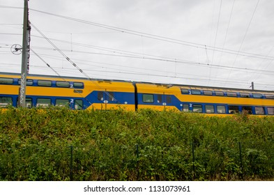 Leiden, Netherlands, 09-07-2018: A train passing by on a cloudy day from the company NS (Dutch train company) in the Netherlands