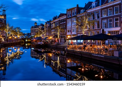 Leiden / Netherlands - 10-22-2019: View during the blue hour from the Koornbrug on the Nieuwe Rijn with Christmas lights (and terrace boats) and the Visbrug in Leiden, Netherlands