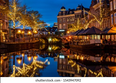 Leiden / Netherlands - 10-22-2019: View on the New Rhine and Visbrug with terrace boats and trees with christmas ornaments during blue hour, Leiden, the Netherlands