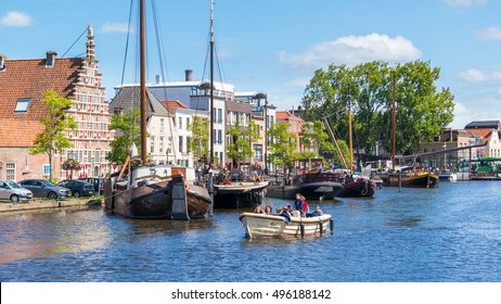 LEIDEN, NETHERLANDS - AUG 9, 2016: People in barge on canal cruise and city wharf Stadstimmerwerf on Galgewater canal in Leiden, South Holland, Netherlands