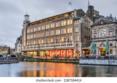 Leiden, The Netherlands, January 7, 2018: the former V&D department store, now Hudson's Bay, with its 1930's brick architecture, reflects in the water of the New Rhine river at dusk