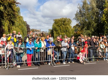 Leiden, Netherlands, October 2018. Audience of children and grown ups waiting behind on the sidewalk behind crush barriers for a parade to pass by