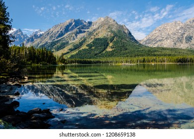 Leigh Lake in the Grand Teton National Park in Wyoming, has beautiful reflections of the Teton peaks and the gorgeous blue sky.