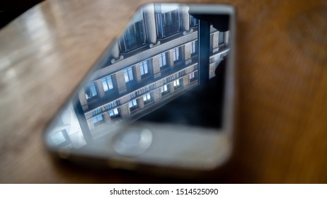 Leipzig, Germany - 14.09.2019: reflected building in phone display on a table - phone on table with reflections of building in it