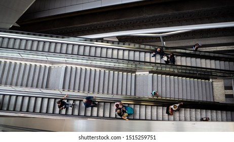 Leipzig, Germany - 14.09.2019:  top view on escalator with people arriving and leaving on escalator at main station near rail track