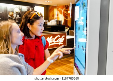 LEIPZIG, GERMANY - MAY 21, 2018: people use self service screens at McDonald's restaurant.