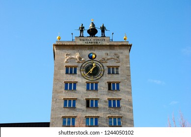 Leipzig, Germany - November 15, 2018 - Krochhochhaus topped by a clock and two muscular bronze sentries, with the motto (in Latin) reading 'Work conquers all' in Leipzig