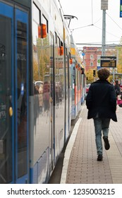 LEIPZIG, GERMANY – OCTOBER 08, 2018: Tram at a stop in the city of Leipzig with a behind running young man