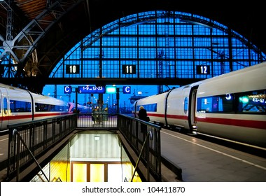 Leipzig train station at night with two speed trains about to leave