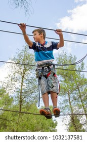 Leisure and activities on nature. Small boy hanging and walking on cables between trees.