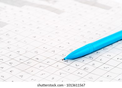 Leisure activity. Close-up of a blue pen on a newspaper crossword puzzle with letters.