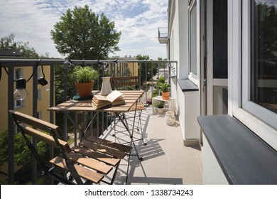 Leisure area on a balcony in a city apartment with wooden table and chairs