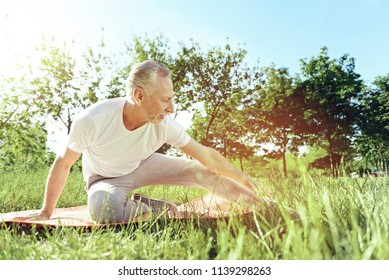 Leisure. Attentive aged man looking happy and healthy while doing morning exercises