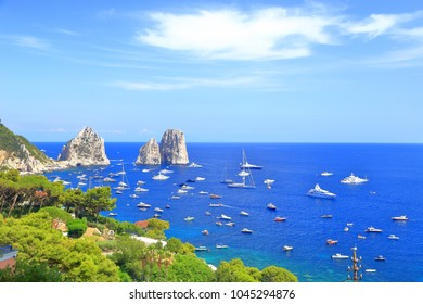 Leisure boats around Faraglioni rocks on Capri island, Italy