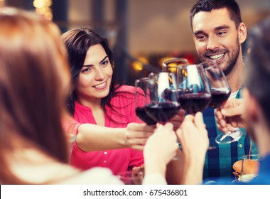 leisure, celebration, drinks, people and holidays concept - happy couple and friends clinking glasses of wine at restaurant