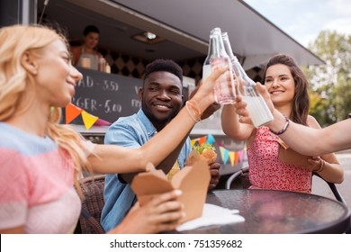 leisure, celebration and people concept - happy friends clinking bottles of non-alcoholic drinks and eating at food truck