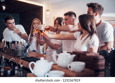 Leisure and communication concept. Group of happy smiling friends enjoying drinks and talking at bar or pub.