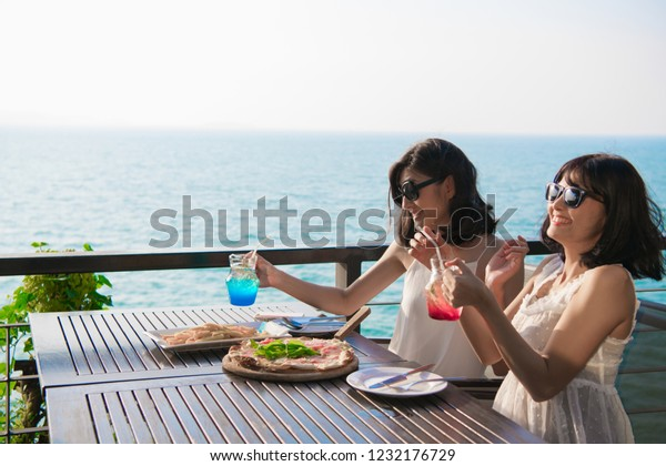 Leisure concept. Beautiful girl is eating at the seaside restaurant. Beautiful girl is enjoying the food on the table.