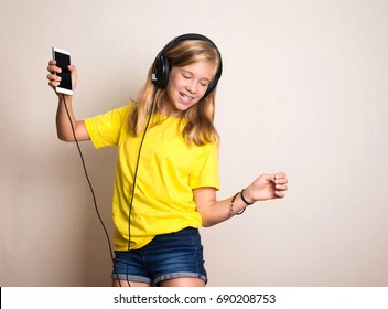 Leisure concept. Happy pre teen or teenage girl in headphones listening to music from smartphone and dancing in her room.