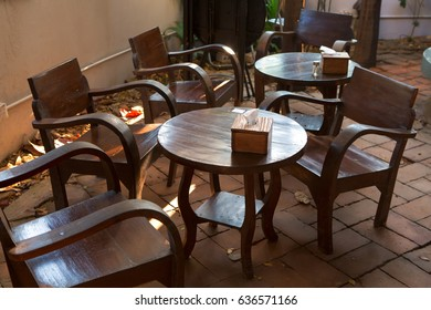 leisure corner with wood chairs and table on brick block floor in coffee shop