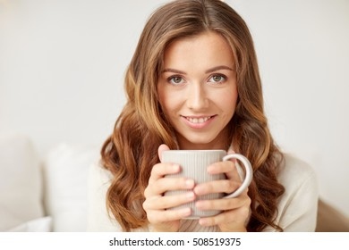 leisure, drink, winter and people concept - close up of happy young woman with cup of coffee or tea at home
