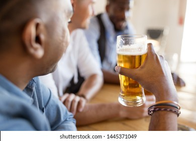 leisure and drinks concept - male friends drinking beer at bar or pub