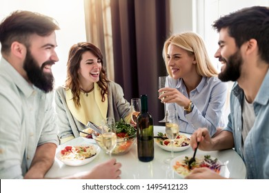 Leisure, eating, food and drink, people and holidays concept-smiling friends having lunch and drinking wine at home.