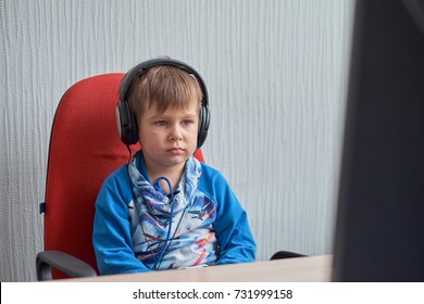 leisure, education, children, technology and people concept - boy with computer and headphones at office - Shutterstock ID 731999158