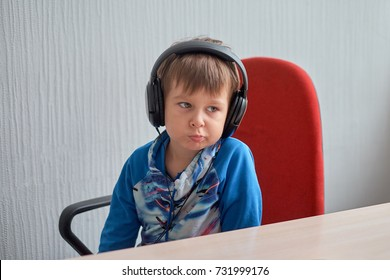 leisure, education, children, technology and people concept - boy with computer and headphones at office - Shutterstock ID 731999176