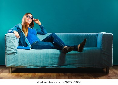 Leisure, education, literature and home concept - Woman in glasses wearing blue denim sitting on couch reading book at home