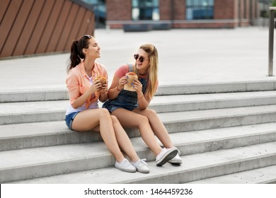 leisure, fast food and friendship concept - happy smiling teenage girls or best friends in sunglasses eating burgers on city street in summer