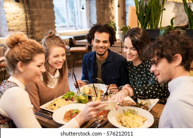 leisure, food, drinks, people and holidays concept - happy friends with smartphone eating and drinking at restaurant