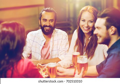 leisure, food and drinks, people and holidays concept - smiling friends eating pizza and drinking beer at restaurant or pub