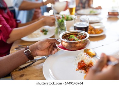 leisure, food and people concept - close up of african american man eating with friends at restaurant