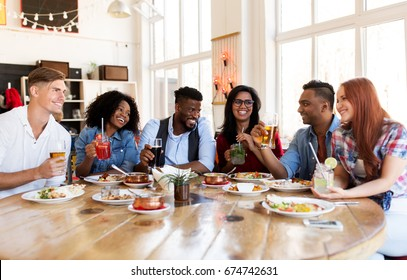 leisure, food and people concept - group of happy international friends with drinks eating and talking at restaurant table