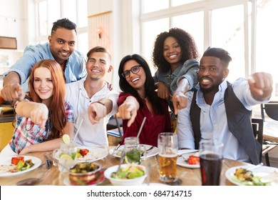 leisure, food and people concept - group of happy international friends eating at restaurant ant pointing finger at you table