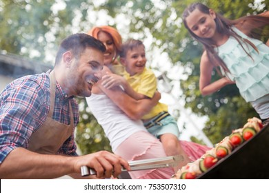 Leisure, food, people and holidays concept-man cooking meat on barbecue grill for his family at summer outdoor party.