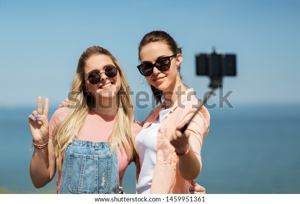 leisure and friendship concept - happy smiling teenage girls or best friends in sunglasses hugging and taking picture by smartphone on selfie stick at seaside in summer