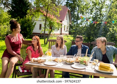 leisure, holidays, communication, people and food concept - happy friends having dinner at summer garden party