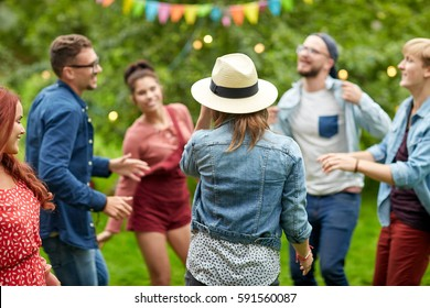 leisure, holidays, fun and people concept - happy friends dancing at summer party in garden
