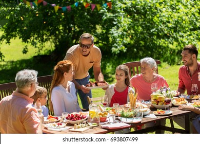 leisure, holidays and people concept - happy family having festive dinner or barbecue party summer garden