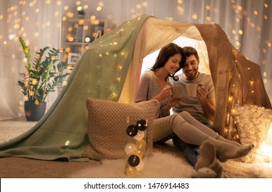 leisure, hygge and people concept - happy couple drinking coffee or tea in kids tent at home