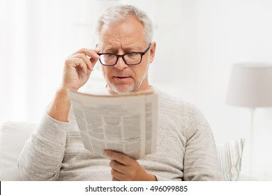 leisure, information, people, vision and mass media concept - senior man in glasses reading newspaper at home