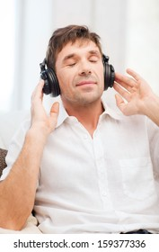 leisure and lifestyle concept - happy man with headphones listening to music at home