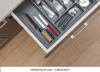 Leisure, lifestyle, domestic life concept. High angle top view cropped photo of open new modern wooden kitchen drawer with different cutlery, spoon, fork, knife