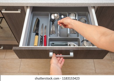 Leisure, lifestyle, domestic life concept. Photo from first person pov view woman hand open new brown kitchen drawer by modern door handle, with different cutlery take spoon to prepare dish food eat