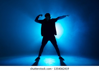 Leisure, lifestyle, hobby and sport. Professional male dancer dancing in night club with smoke and blue neon lights with flare in centre